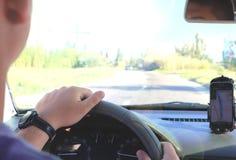 Mężczyzna w samochodzie i trzymać czarnego telefon komórkowego z map gps nawigacją, tonującą przy zmierzchem fotografia stock