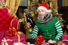 Mężczyzna w Santa kapeluszowym uśmiechu z szampańską butelką Obrazy Royalty Free