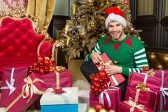 Mężczyzna w Santa kapeluszu z teraźniejszość przy choinką Zdjęcia Royalty Free
