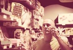 Mężczyzna w sklepów wezwaniach żona Zdjęcie Stock