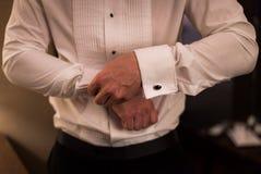 Mężczyzna w smokingowej koszula robi w górę cufflinks fotografia royalty free