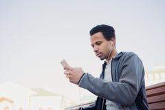 Mężczyzna w sportach mundur i hełmofony słucha muzyka używać smartphone zdjęcie stock