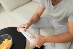 Mężczyzna w szarość domowych ubraniach jest siedzący na odpoczywać i kanapie TV pilot do tv Fotografia Royalty Free