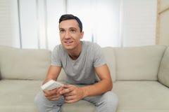 Mężczyzna w szarość domowych ubraniach jest siedzący na odpoczywać i kanapie TV pilot do tv Obrazy Royalty Free