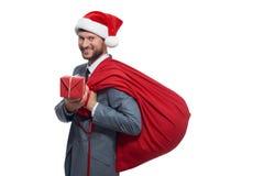 Mężczyzna w szarym apartamencie jak Santa Claus daje pudełku z prezentem Obrazy Stock
