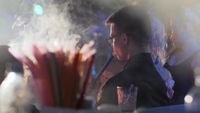 Mężczyzna w szkłach dymi nargile w na wolnym powietrzu, samiec odpoczywa z nargile w rękach przy wieczór wydarzeniem w eyeglasses zbiory