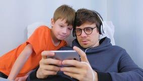 Mężczyzna w szkłach i hełmofonach bawić się grę w smartphone z jego synem Gamer relaksuje zbiory