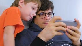 Mężczyzna w szkłach i hełmofonach bawić się grę w smartphone z jego synem Gamer relaksuje zdjęcie wideo