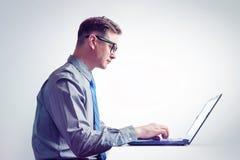 Mężczyzna w szkłach, koszula i krawacie, pracuje na laptopie, boczny widok Zdjęcia Royalty Free