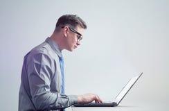 Mężczyzna w szkłach, koszula i krawacie, pracuje na laptopie, boczny widok Zdjęcia Stock