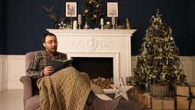 Mężczyzna w szkłach w krześle czyta książkę w domu przy Bożenarodzeniowym czasem za głośnym Bożenarodzeniowy iterior zdjęcie royalty free