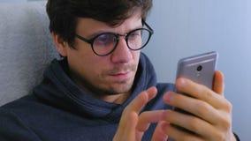 Mężczyzna w szkłach pisać na maszynie wiadomość w ogólnospołecznych środkach na smartphone Twarz i telefon w górę zbiory wideo