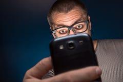 Mężczyzna w szkieł spojrzeniach przy jego smartphone Fotografia Stock