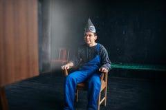 Mężczyzna w tinfoil kapeluszu siedzi w krześle, paranoi pojęcie obraz stock