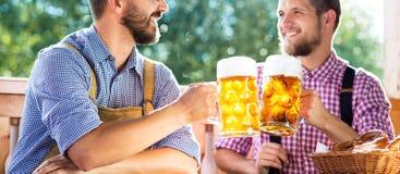 Mężczyzna w tradycyjnego bavarian mienia odzieżowych kubkach piwo fotografia royalty free