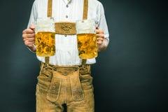 Mężczyzna w tradycyjnego bavarian mienia odzieżowym kubku piwo zdjęcia royalty free