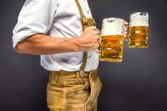 Mężczyzna w tradycyjnego bavarian mienia odzieżowym kubku piwo zdjęcie stock