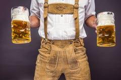 Mężczyzna w tradycyjnego bavarian mienia odzieżowym kubku piwo zdjęcie royalty free