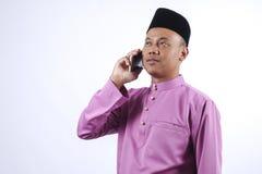 Mężczyzna w tradycyjnej odzieży z smartphone świętuje Eid Fitr Zdjęcia Royalty Free