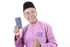 Mężczyzna w tradycyjny ubraniowy rozochoconym z pieniądze paczką podczas świętuje Eid Fitr Fotografia Royalty Free