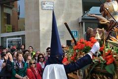 Mężczyzna w tradycyjnym kostiumowym nakryciu jego twarz bije dzwon podczas tradycyjnego Wielkanocnego korowodu Semanа Santa obrazy stock