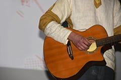 Mężczyzna w tradycyjnym kostiumu bawić się gitarę obraz royalty free