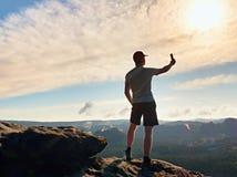 Mężczyzna w tshirt i skrótach bierze fotografie z mądrze telefonem na szczycie rockowy imperium Obrazy Stock