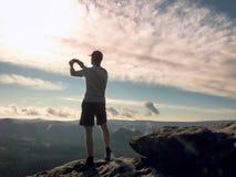 Mężczyzna w tshirt i skrótach bierze fotografie z mądrze telefonem na szczycie rockowy imperium Zdjęcie Royalty Free