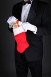 Mężczyzna w Tux z Bożenarodzeniową pończochą fotografia stock