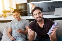 Mężczyzna w urodzinowych kapeluszach pokazują each inne teraźniejszość Zdjęcia Stock