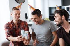 Mężczyzna w urodzinowych kapeluszach pokazują each inne teraźniejszość Zdjęcia Royalty Free