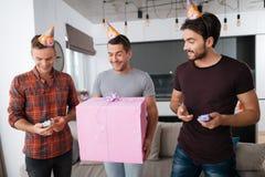 Mężczyzna w urodzinowych kapeluszach pokazują each inne teraźniejszość Obraz Royalty Free