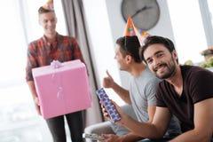 Mężczyzna w urodzinowych kapeluszach pokazują each inne teraźniejszość Zdjęcie Stock