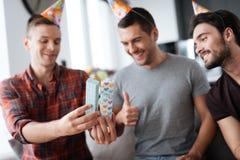 Mężczyzna w urodzinowych kapeluszach pokazują each inne teraźniejszość Zdjęcie Royalty Free