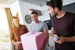 Mężczyzna w urodzinowych kapeluszach pokazują each inne teraźniejszość Obrazy Royalty Free