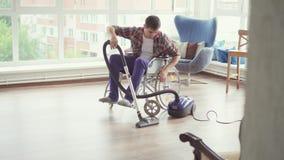 Mężczyzna w wózku inwalidzkim czyścił z próżniowym cleaner zdjęcie wideo
