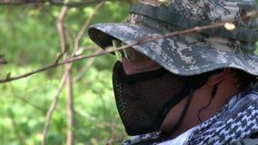 Mężczyzna w wojskowych uniformach bawić się na airsoft militarnym wieloboku w lesie