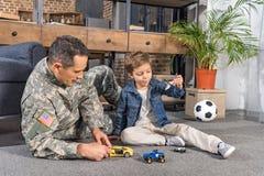 mężczyzna w wojskowym uniformu i małym synu bawić się z zabawkami wpólnie zdjęcia royalty free