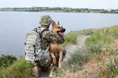 Mężczyzna w wojskowym uniformu z Niemieckim pasterskim psem outdoors Zdjęcia Stock