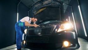 Mężczyzna w workwear naprawia samochód zbiory wideo