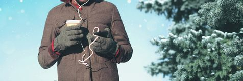 Mężczyzna w zima dniu z smartphone słucha muzyczny trzyma filiżankę zdjęcie stock
