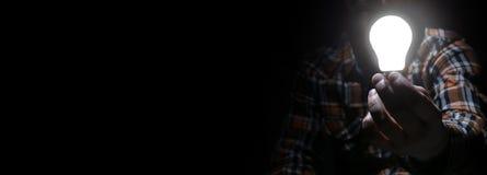 Mężczyzna w zmroku z jarzeniową żarówką Fotografia Royalty Free