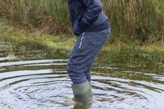 Mężczyzna watolina przez wodnych jest ubranym Wellington butów zdjęcie stock