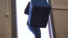 Mężczyzna wchodzić do dużego błękitnego zbiornika z rękojeścią w budynek od ulicy deliveryman dostawa shipwreck zdjęcie wideo