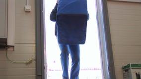 Mężczyzna wchodzić do dużego błękitnego zbiornika z rękojeścią w budynku od ulicy, stawia je w podłoga deliveryman dostawa zdjęcie wideo