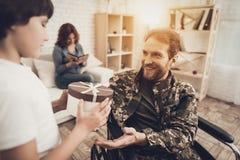 Mężczyzna weteran W wózka inwalidzkiego powrót do domu pojęciu fotografia stock