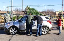 Mężczyzna wiąże choinki na górze SUV podczas gdy kobieta ogląda one w żywym choinka udziale w Tulsa, Oklahoma usa 1 obrazy stock