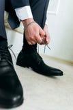 Mężczyzna wiąże koronki na jego czarnych butach fotografia stock
