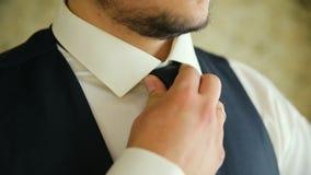 Mężczyzna wiąże krawat blisko okno w białej koszula Zakończenie zdjęcie wideo