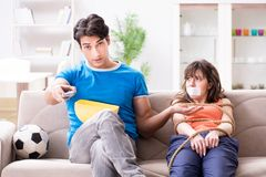 Mężczyzna wiąże w górę jego żony oglądać sporty futbolowych Obrazy Stock